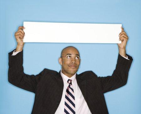 Photo pour Afro-américain tient pancarte blanche sur fond bleu. - image libre de droit