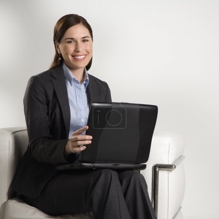Photo pour Caucasien milieu professionnel adulte femme assis dans le bureau moderne travaillant sur ordinateur portable visionneuse en regardant et en souriant. - image libre de droit