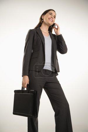 Photo pour Caucasien milieu professionnel adulte femme tenant le porte-documents, parler sur téléphone portable et souriant. - image libre de droit