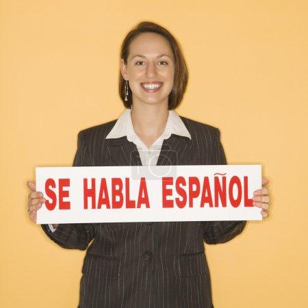 "Caucasian businesswoman smiling holding sign reading ""se habla espanol."""