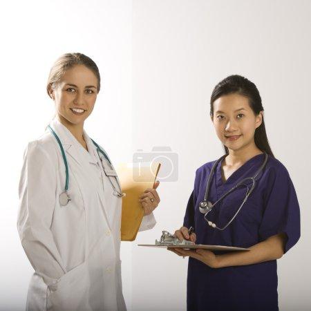 Photo pour Caucasien mid-adult female doctor et asiatique chinois adjoint d'au médecin femelle de mid-adult debout ensemble souriant et regardant la visionneuse - image libre de droit
