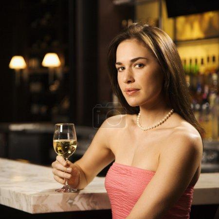 Photo pour Milieu adulte femme caucasienne, assis au bar avec verre de vin blanc en regardant visionneuse. - image libre de droit