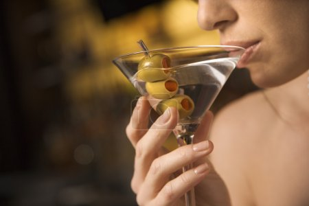 Photo for Close up of mid adult Caucasian woman drinking a martini with three olives. - Royalty Free Image