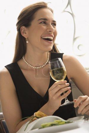 Foto de Mujer caucásica adulta media sonriendo y bebiendo vino blanco en restaurante. - Imagen libre de derechos