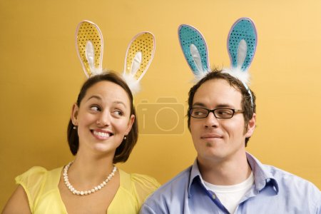 Caucasian mid adult couple wearing rabbit ears and...