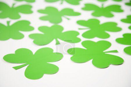 Photo for Group of green paper shamrocks on white. - Royalty Free Image