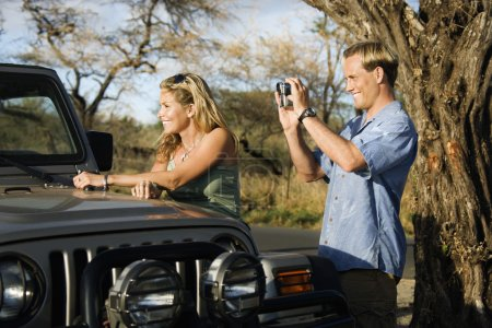 Photo for A woman leans on an SUV while a man uses a video camera to capture the scenery. Horizontal format. - Royalty Free Image
