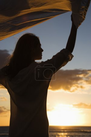Photo for Attractive Caucasian mid-adult woman holding up fabric in breeze silhouetted by sunset beside ocean. - Royalty Free Image