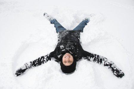 Woman making snow angel.