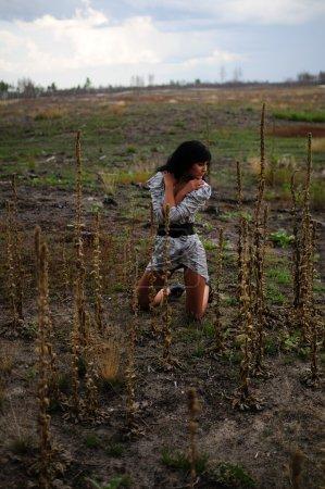 Woman Kneeling In Open Field