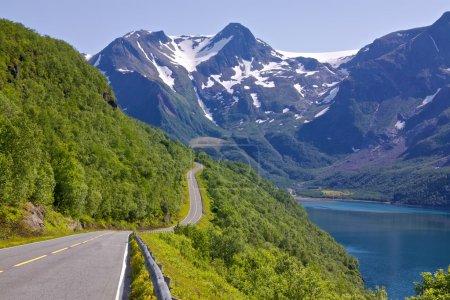 Photo pour Route côtière en Norvège menant à Bodo avec des montagnes enneigées du parc national Saltfjellet-Svartisen en arrière-plan - image libre de droit