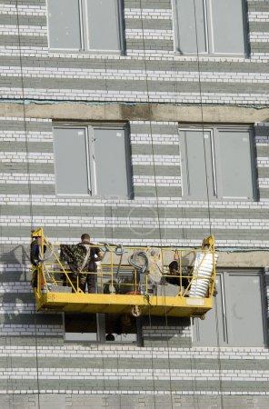 Builders in suspended platform on facade