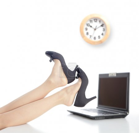 Photo for Relax Time in office, business woman take off high heels shoes with office background and a clock - Royalty Free Image