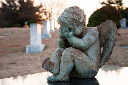Photo pour Ange de bébé qui pleure dans cimetière protégeant sa tombe. pris au lever du soleil avec une faible profondeur de champ. - image libre de droit