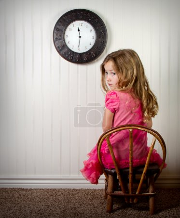 Photo for Little girl in time out or in trouble looking, with clock on the wall - Royalty Free Image