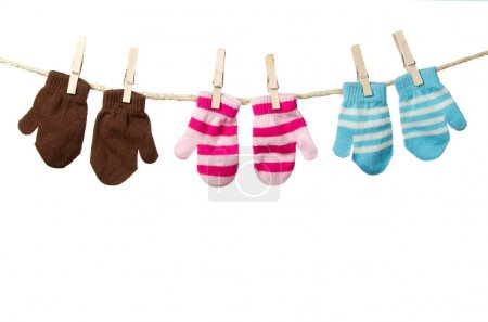 Photo for Three mittens hanging on a clothes line, brown mittens, pink striped mittens and blue striped mittens. Isolated on white background. - Royalty Free Image
