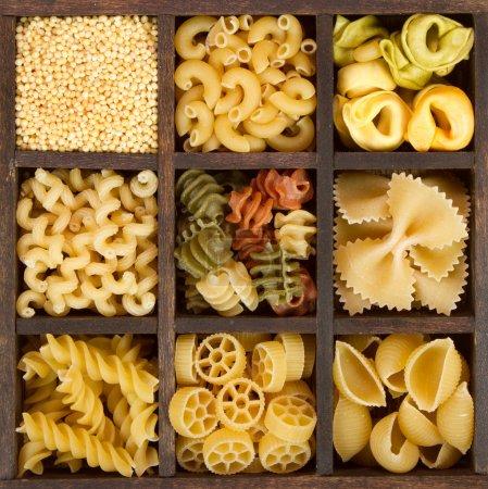 Photo pour Un assortiment de pâtes italiennes, neuf variétés différentes, séparées dans une boîte décorative - image libre de droit