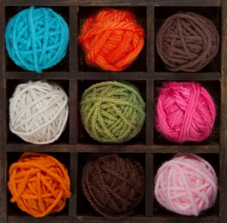 Nine colorful balls of yarn in printers box
