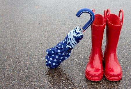 Photo pour Bottes de pluie rouges et parapluie à pois sur chaussée mouillée - image libre de droit
