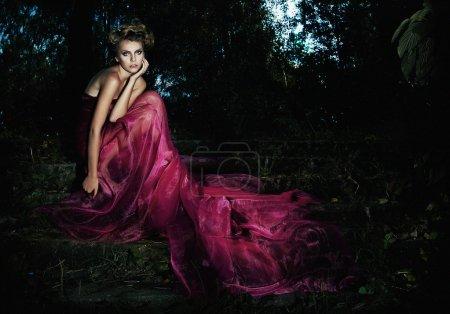 Photo pour Soir scénique - Fée en robe longue assise sur l'escalier dans la forêt sombre - série de photos - image libre de droit