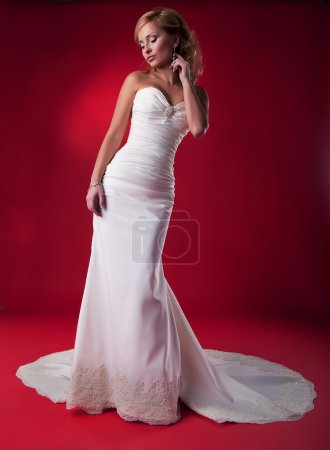 Pretty bride in white wedding long dress on red background posing