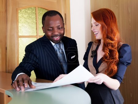 Red hair young businesswoman and black american businessman in office space