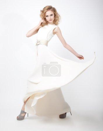 Beautiful woman blonde in flying vernal white dress