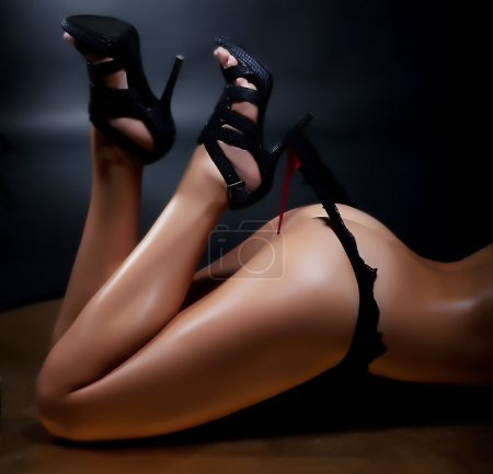 Photo for Beautiful woman's legs in heels pulling her black lingerie. Lovely buttocks - Royalty Free Image