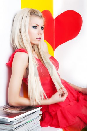 Sexy young female blonde posing in studio over red heart