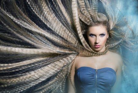Photo pour Jeune belle fille avec de longs cheveux ondulés agitant dans la fumée est dans le bleu - image libre de droit