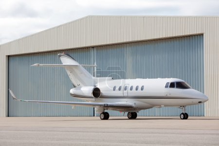 Private jet parked in front of hangar