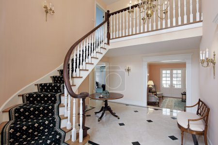 Photo for Salmon colored foyer with curved staircase and carpeted stairs - Royalty Free Image