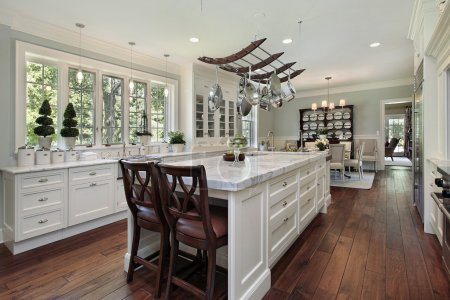 Kitchen in luxury home with white granite island...