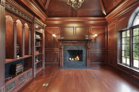 Photo pour Élégante bibliothèque dans une maison de luxe avec cheminée en marbre noir - image libre de droit