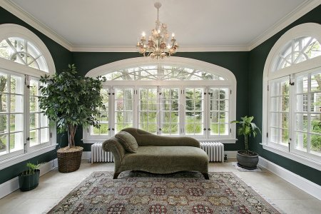 Photo for Sun room in luxury home with sofa and wall of windows - Royalty Free Image