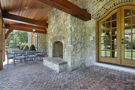 Brick patio with stone fireplace