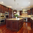 Kitchen in luxury home with cherry wood cabinetry...