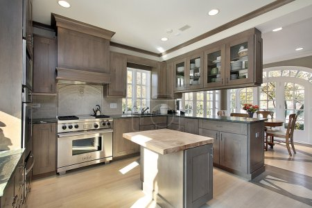 Kitchen in remodeled home with wood cabinetry and ...