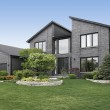 Modern home with gray brick and black door...