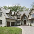 Large luxury home with shingle roof and brick driv...