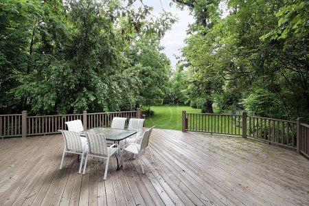 Photo pour Grande terrasse en bois avec table et chaises menant à l'arrière-cour - image libre de droit