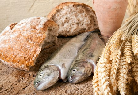 Photo for Wine jug, bread and fish as symbols of christian religion - Royalty Free Image