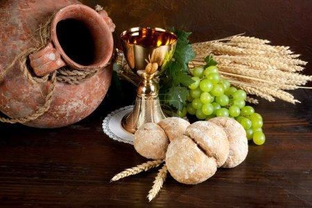 Photo pour Raisins et pain à côté d'un calice doré avec vin - image libre de droit