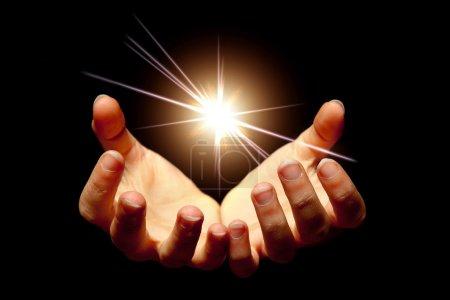 Photo pour Les mains féminines tenant une étoile brillante dans l'obscurité - image libre de droit