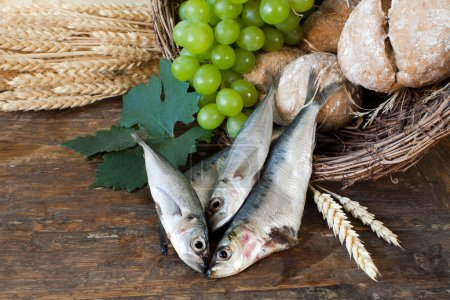 Photo for Bread and fish with wine grapes symbolizing the miracles of Jesus Christ - Royalty Free Image
