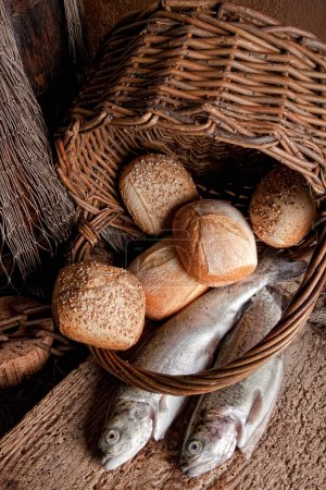 Photo for Religious still life of loaves of bread, fishing net, basket and two fresh fish - Royalty Free Image