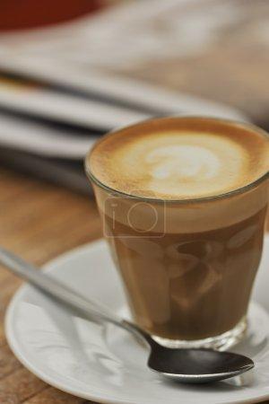 Photo pour Un café latte sur une table dans un café, avec du papier journal dans le fond, faible profondeur de champ, de belles tons bruns - image libre de droit