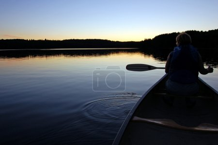 Photo for Sunset and canoe trip in calm lake in Algonquin Park - Royalty Free Image