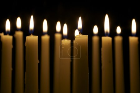 Photo for Several tall candles lit in a dark room. - Royalty Free Image