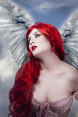 Beautiful sexy angel with wings, red long hair woman